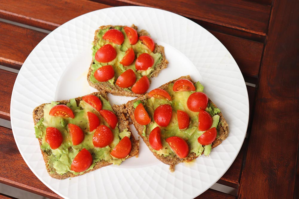 Sprouted Ezekiel Bread topped with tomatoes and avocado on a white plate